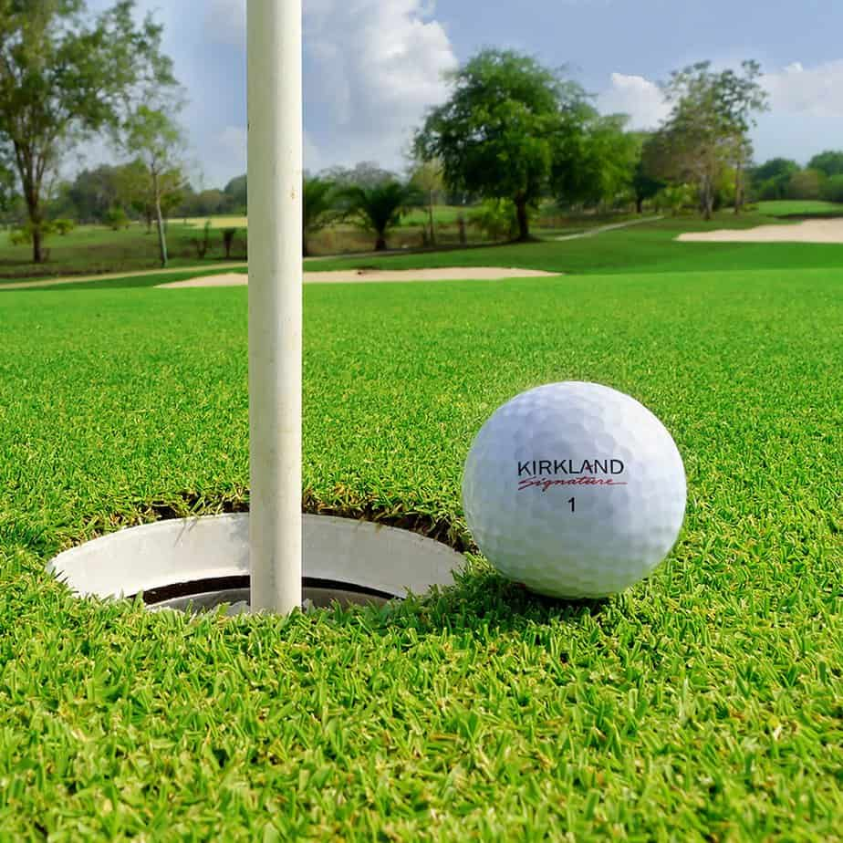 Image of a Kirkland Signature golf ball next to a golf hole on the green.